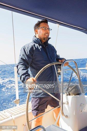 Sailing  Men skipper on a rudder of a sailboat