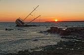 Sailboat, stranded along the coast on the cliff of Sardinia in the Mediterranean Sea.