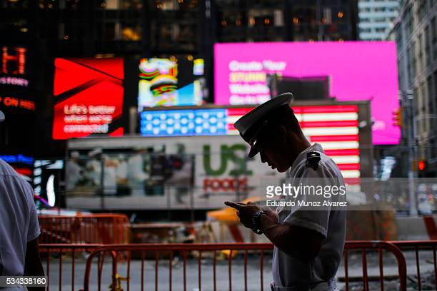 Sailor checks his mobile phone as he walks around Times Square during Fleet Week on May 25 2016 in New York City Nearly 4500 Sailors Marines and...