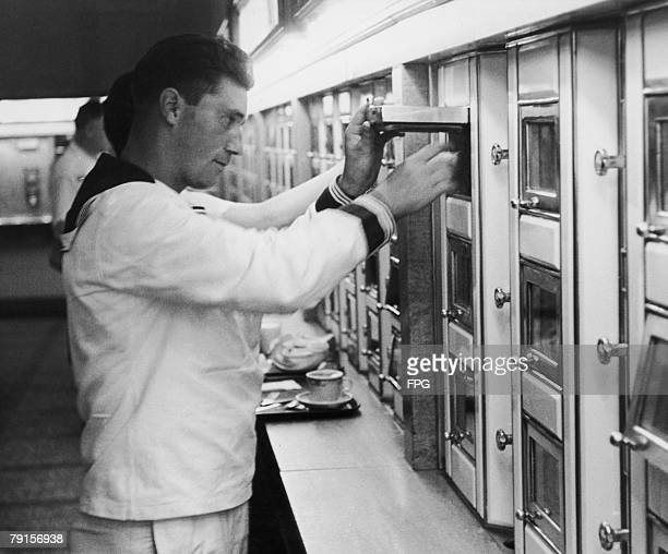A sailor helps himself to food from an automated selection in a self service canteen circa 1950