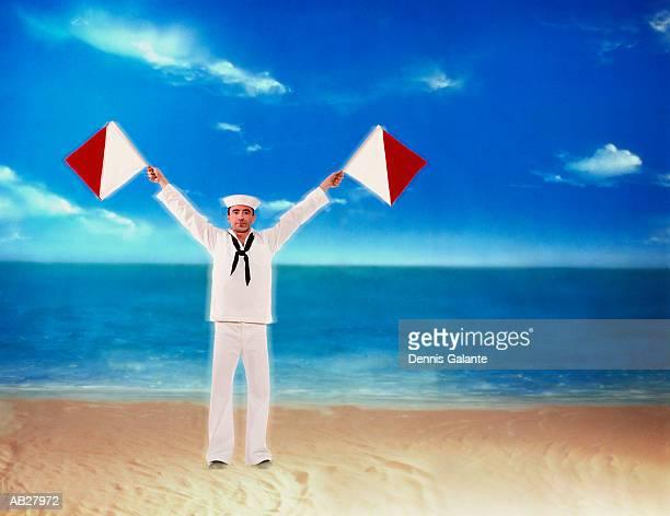 Sailor holding semaphore flags on beach (digital composite)