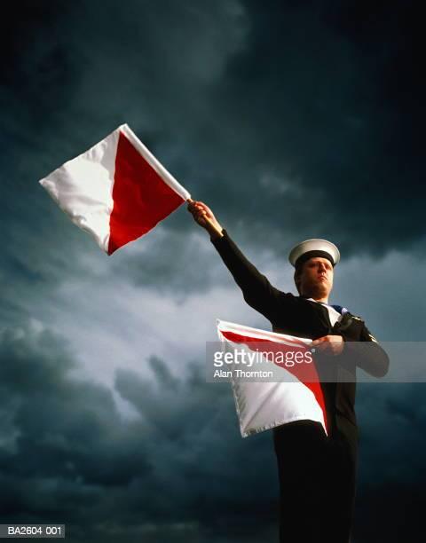 Sailor in naval uniform using semaphore, against stormy sky