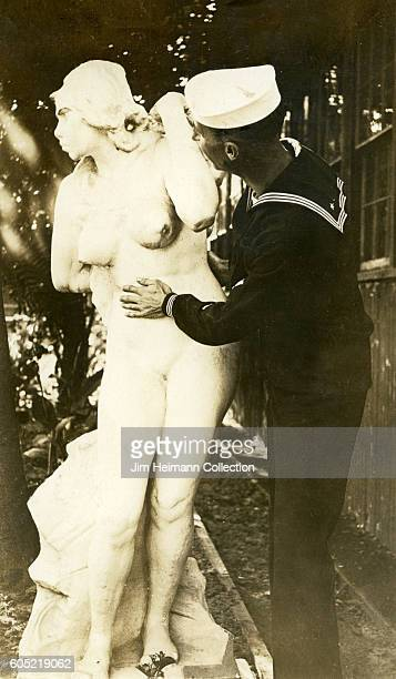 Sailor looking at and tenderly touching female statue outdoors in front of building
