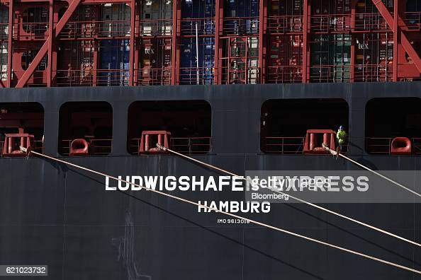 A sailor looks out from the Ludwigshafen Express container vessel operated by HapagLloyd AG as it arrives on the dockside at the container terminal...