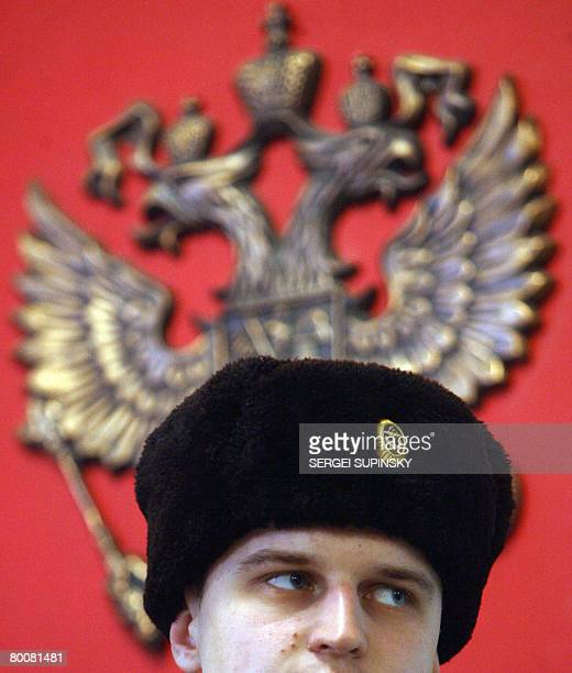 A sailor of the Russian Navy stays in front of the state emblem as he votes in a polling station in Sevastopol a military base of the Russian Black...