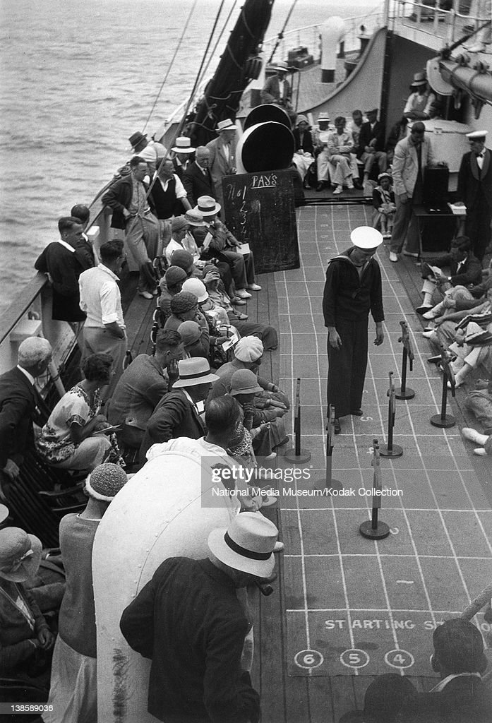 Sailor on board a sea borne liner operating a horse racing game for the amusement of the passengers c1930s