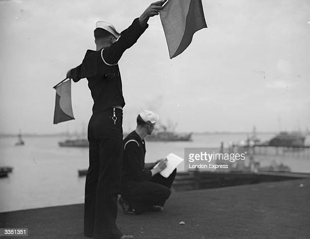 A sailor on shore signals to ship by semaphore whilst another takes notes