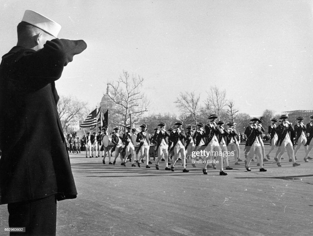 A sailor salutes a procession of Lexington Minutemen as they march down Pennsylvania Avenue during the parade for President John F. Kennedy's inauguration in Washington, D.C. on Jan. 20, 1961.