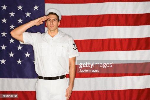 Sailor saluting and American flag : Stock Photo