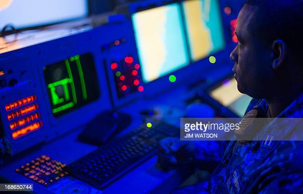A sailor sits within the Combat Information Center aboard the Arleigh Burkeclass guided missile destroyer USS Stout at Naval Station Norfolk in...