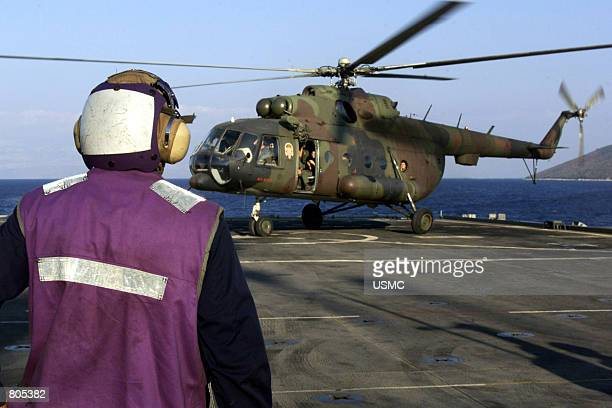 Sailor watches an M18 Croatian helicopter land September 26 2000 on the flight deck of the amphibious assault ship USS Austin Sailors and Marines...
