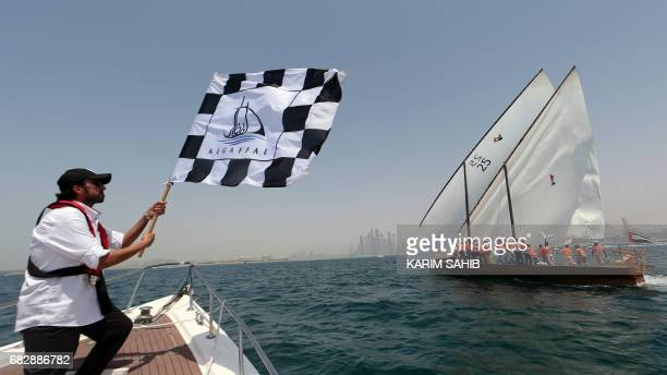 A sailor waves a flag at the finish line of alGaffal traditional longdistance dhow sailing race as the crew of Zilzal a dhow captained by Sheikh...