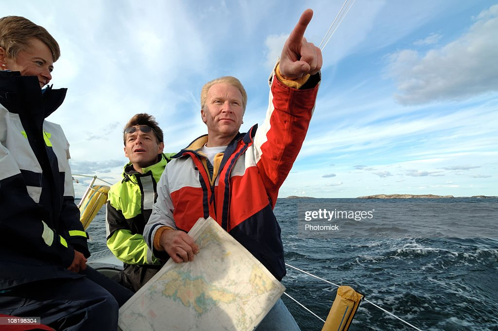 Sailor pointing forward, chart in hand.