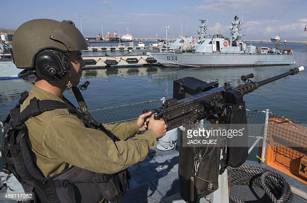 A sailor with the Israeli navy takes a position at a machine gun on a Dvora vessel as it leaves the port in Ashdod on November 17 2014 Israel uses a...