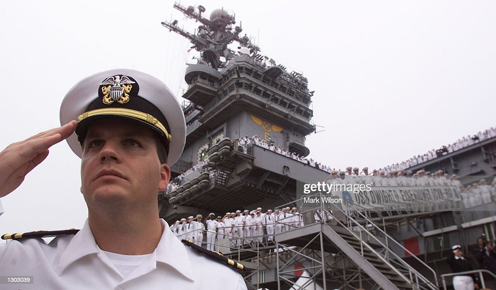 Sailors aboard the aircraft carrier USS Dwight D.Eisenhower salute during the playing of the national anthem during a memorial service October 18, 2000 in Norfolk VA. President Clinton attended the service that honored the wounded and dead from the U.S. navy destroyer USS Cole that was bombed while on a refueling stop in the Yemeni port of Aden.