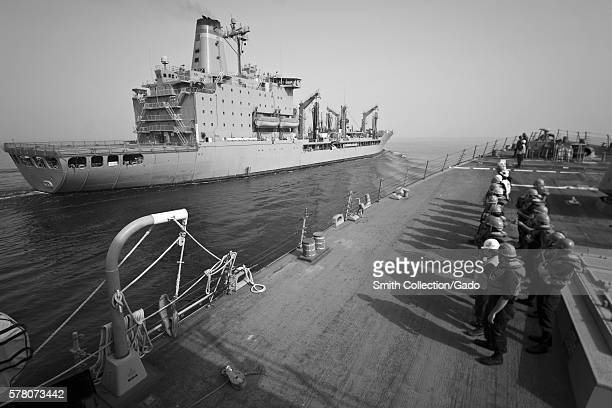 Sailors aboard the guidedmissile destroyer USS Porter DDG 78 stand by to conduct a replenishment at sea with the Military Sealift Command fleet...