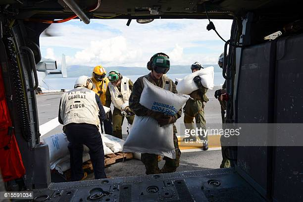 Sailors and Marines attached to Joint Task Force Matthew load food aboard the amphibious assault ship USS Iwo Jima for delivery onto an MH60S Sea...