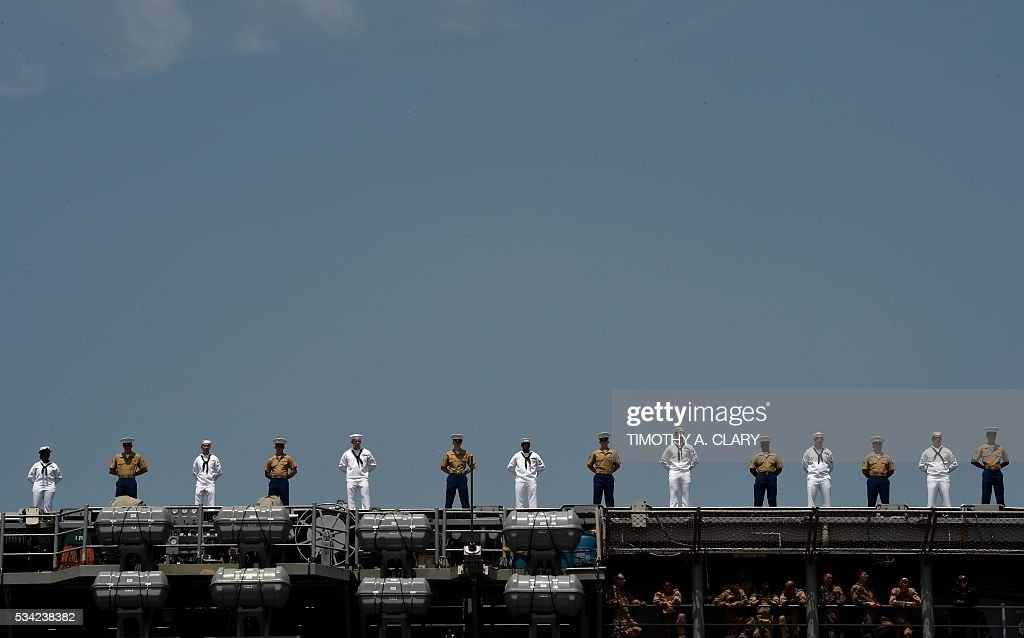 Sailors and marines stand on the deck of the USS Bataan (LHD 5) as it arrives into Pier 88 during the 'Parade of Ships' ceremony to kick off Fleet Week in New York on May 25, 2016. Thousands of sailors, marines and Coast Guardsmen from the US Navy and US Coast Guard as well as from international navy ships attend the celebrations. / AFP / TIMOTHY
