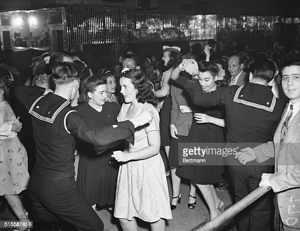Sailors and their girlfriends dance in Times Square to celebrate the surrender of Japan