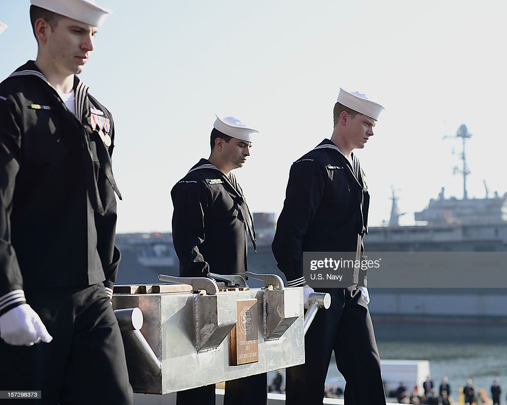 Sailors assigned to the aircraft carrier USS Enterprise (CVN 65) carry a time capsule filled with messages and mementos for the crew of the next ship to carry the Enterprise name during the ship's inactivation ceremony on December 1, 2012 in Norfolk Virginia.. Enterprise was commissioned in 1961 and is scheduled to celebrate her inactivation after 51 years of service.