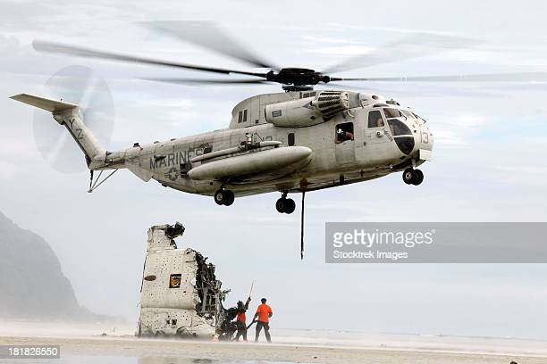 U.S. Sailors assist a CH-53D Sea Stallion helicopter in removing wreckage.