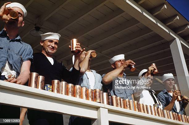 Sailors enjoy large quantities of Ballantine's beer and planters peanuts on the deck of the US Naval Battleship USS Iowa known as 'The Big Stick' in...