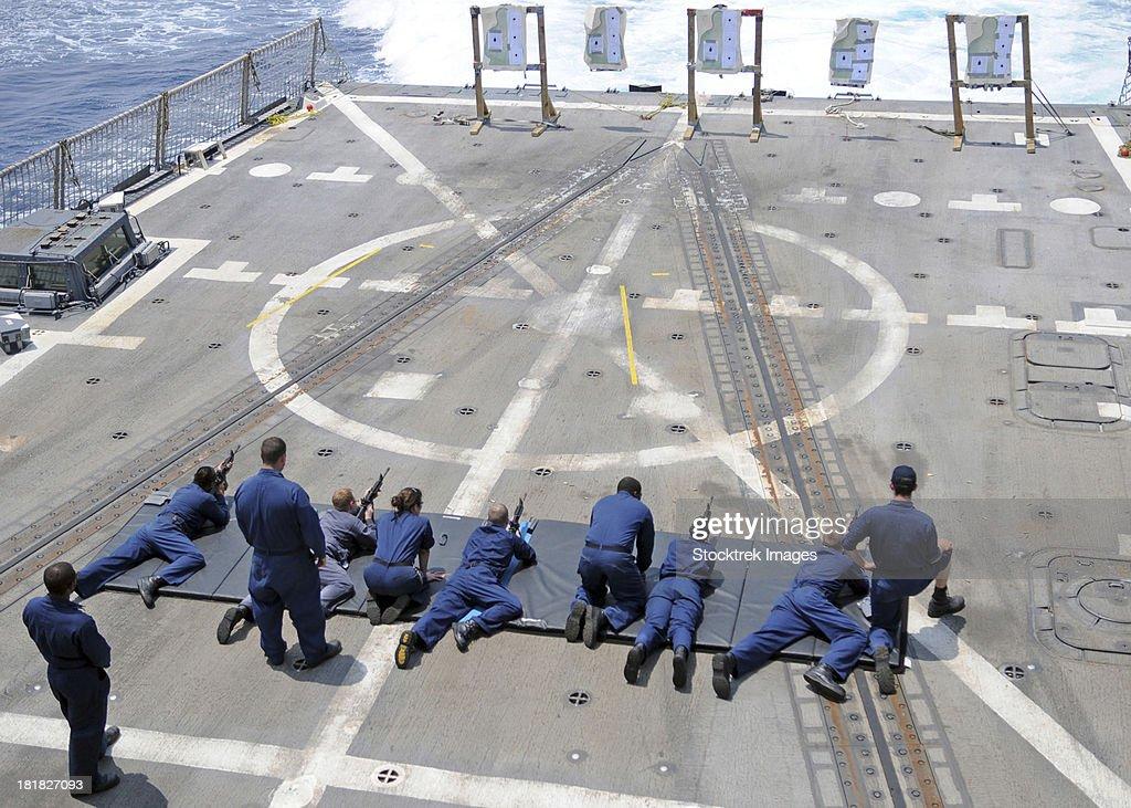 Sailors fire M4A1 carbine assault rifles aboard USS Halsey.