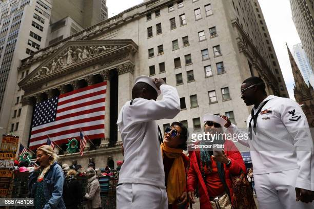Sailors from the USS Kearsarge pose for photos with tourists along Wall Street on May 26 2017 in New York City Now in its 29th year Fleet Week brings...