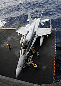 Pacific Ocean, March 2, 2011 - Sailors move an F/A-18C Hornet from the elevator into the hangar bay aboard USS Ronald Reagan.