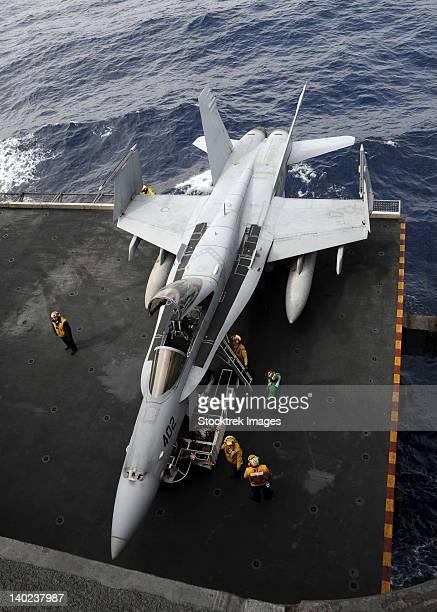 Sailors move an F/A-18C Hornet into the hangar bay.