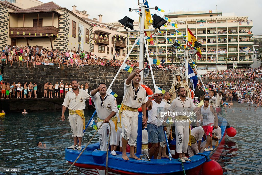 Sailors of the New saint Ramon boat and Carriers of the Great God Power brotherhood leave Puerto de la Cruz dock carrying the Virgen del Carmen statue to its journey on July 15, 2014 on the Canary island of Tenerife, Spain. Since 1921, the statue of the Virgen del Carmen, patron saint of fishermen, has been carried with great fanfare annually as part of July Festivities to the Puerto de la Cruz dock where, at the end of its procession, it is hoisted aboard a decorated boat. Weather permitting, the boat carrying the statue, accompanied by a flotilla of other boats, makes a short journey along the island coast before returning to the harbour. In recent years, attendance at the event has numbered more than 35,000 people.