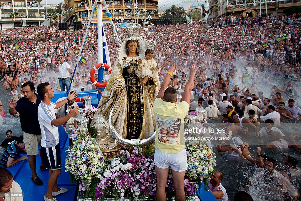 Sailors of the New saint Ramon boat celebrate with the corwd the loading of the Virgen del Carmen statue for its journey on July 15, 2014 at Puerto de la Cruz dock on the Canary island of Tenerife, Spain. Since 1921, the statue of the Virgen del Carmen, patron saint of fishermen, has been carried with great fanfare annually as part of July Festivities to the Puerto de la Cruz dock where, at the end of its procession, it is hoisted aboard a decorated boat. Weather permitting, the boat carrying the statue, accompanied by a flotilla of other boats, makes a short journey along the island coast before returning to the harbour. In recent years, attendance at the event has numbered more than 35,000 people.
