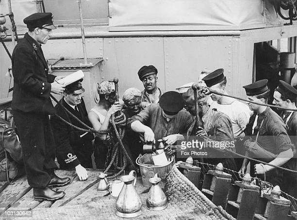 Sailors of the Royal Navy are issued with a rum ration aboard the 'HMS Kellett' 1942