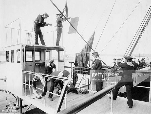 Sailors on a ship are using semaphore flags to give signals to another ship 1900 Photographer A Renard Vintage property of ullstein bild