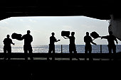 Pacific Ocean, April 14, 2011 - Sailors pass chemical, biological and radiological kits during a working party in the hangar bay of the aircraft carrier USS Ronald Reagan (CVN-76).