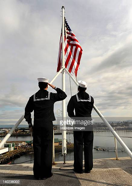 Sailors raise the national ensign aboard USS Abraham Lincoln.