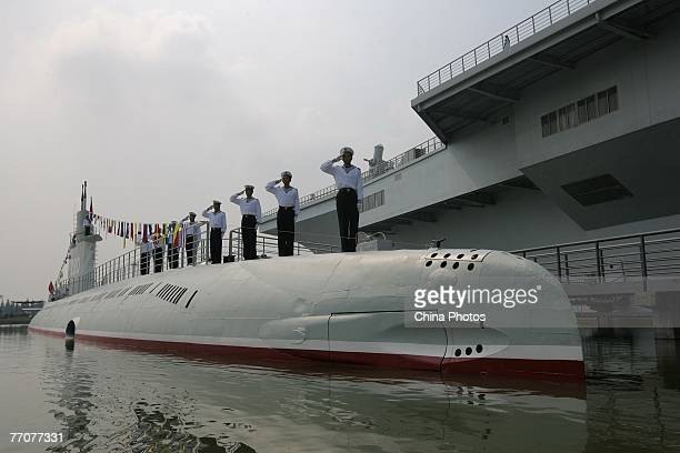 Sailors salute on top of a retired Chinese submarine at the Military Education Center an exhibition space of military euqipment and vehicles housed...