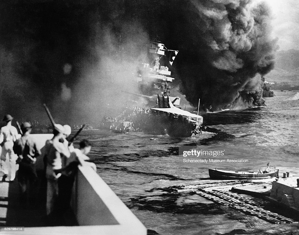 Sailors scramble to escape the sinking battleship USS California after a surprise attack by the Japanese