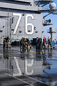 Pacific Ocean, March 23, 2011 - Sailors scrub the flight deck aboard the aircraft carrier USS Ronald Reagan (CVN-76) following a countermeasure wash down to decontaminate the flight deck while the shi