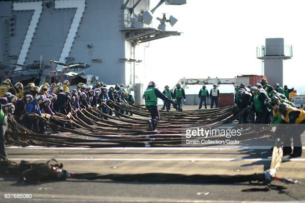 Sailors set up the aircraft barricade during a training exercise on the flight deck abroad the aircraft carrier USS George H W Bush January 7 2013...