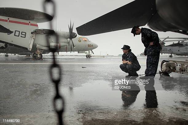 US sailors shelter beneath the wing of an aircraft on the flight deck of the USS Carl Vinson aircraft carrier during a heavy rainstorm in Hong Kong...