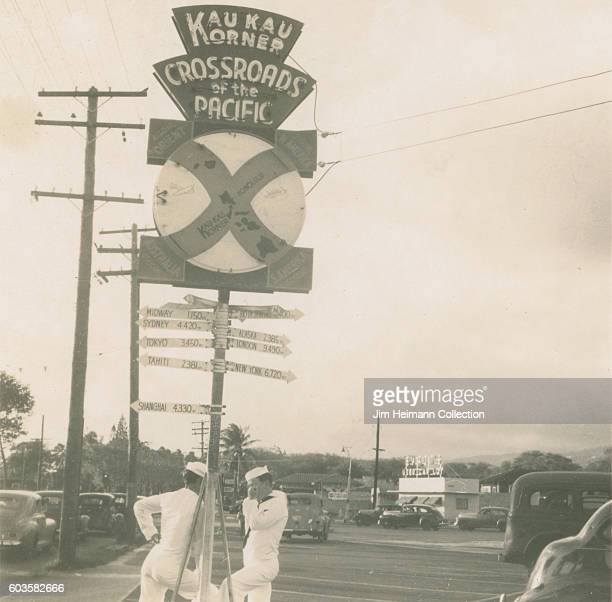 Sailors standing by Crossroads of the Pacific sign Numerous parked cars