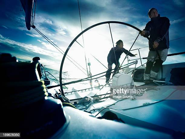 Sailors steering yacht