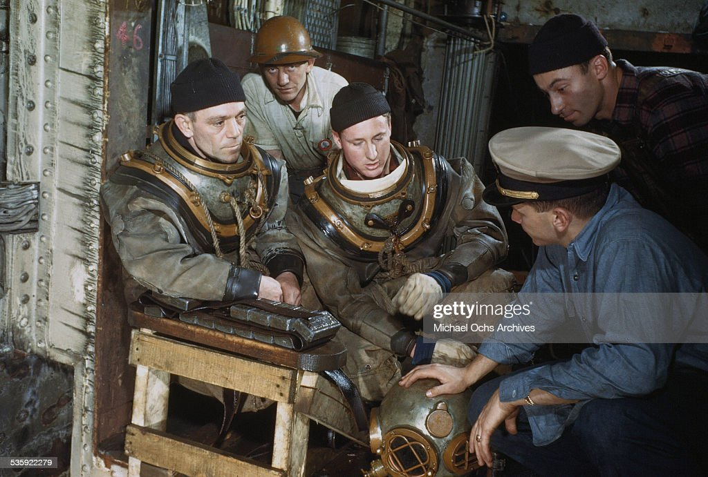 Sailors with diving suits get ready to dive to inspect the SS Normandie a former French luxury liner which was seized by U.S. and renamed USS Lafayette, caught fire while transforming the ship into a U.S. troopship and listed port side, at New York Pier 88 in New York. To costly to restore it was scrapped in 1946.