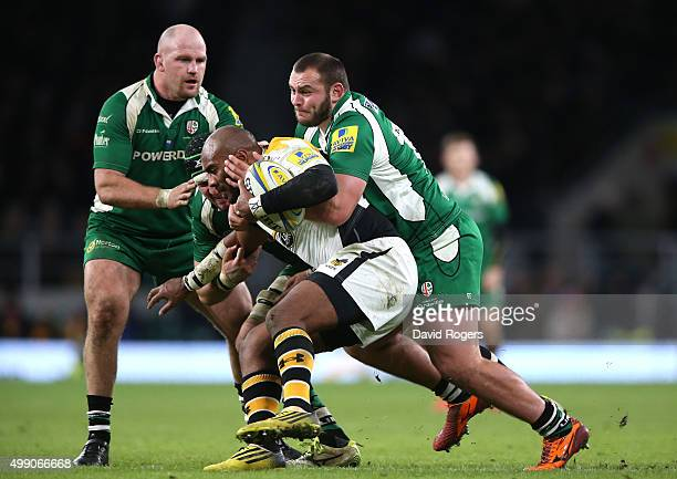 Sailosi Tagicakibau of Wasps is tackled by Gerard Ellis and Ben Franks during the Aviva Premiership match between London Irish and Wasps at...