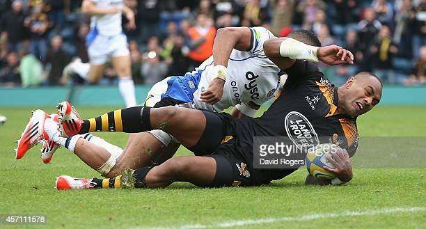 Sailosi Tagicakibau of Wasps stretches to score a try despite being held by Anthony Watson during the Aviva Premiership match between Wasps and Bath...