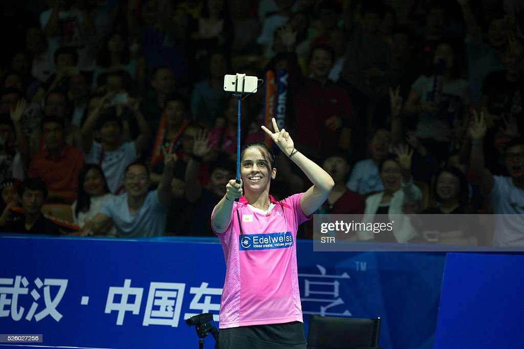 Saina Nehwal of India uses selfie sticks to take photos with fans after winning the women's singles quarter-final match against Wang Shixian of China at the 2016 Badminton Asia Championships in Wuhan, central China's Hubei province on April 29, 2016. / AFP / STR
