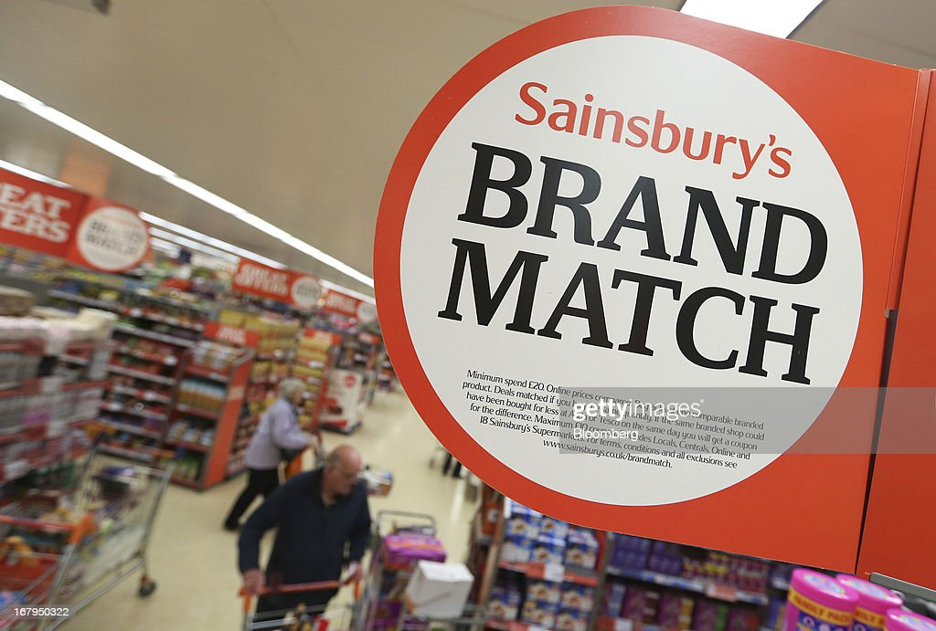 A Sainsbury's 'Brand Match' campaign logo sits on a sign inside a J Sainsbury Plc supermarket store in Godalming, U.K., on Thursday, May 2, 2013. J Sainsbury Plc, the U.K.'s third-largest supermarket chain, will report full year results on May 8. Photographer: Chris Ratcliffe/Bloomberg via Getty Images