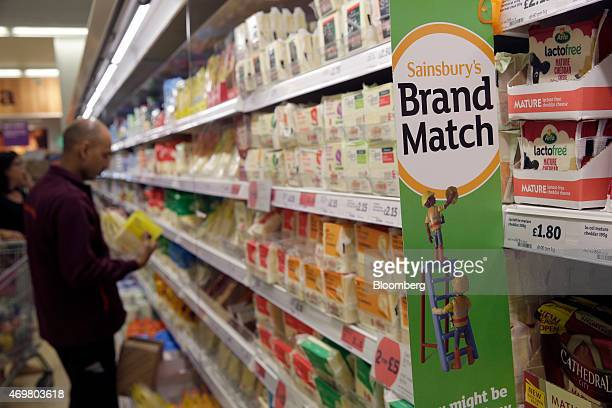 A Sainsbury's 'brand match' promotional poster hangs in a chiller cabinet as an employee restocks cheeses in the dairy aisle of a Sainsbury's...