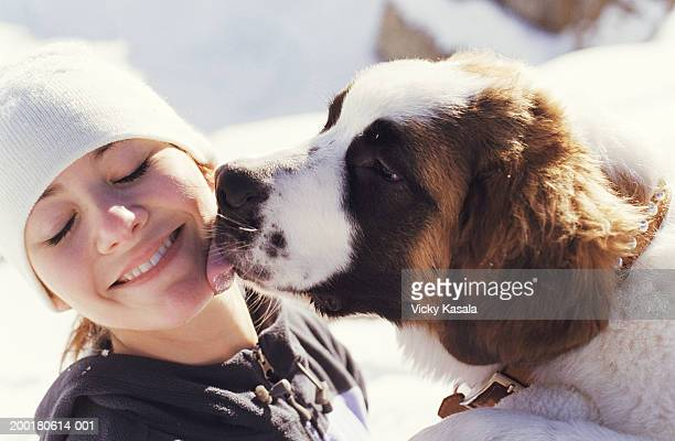 Saint Bernard licking teenage girl's (16-18) face, close-up